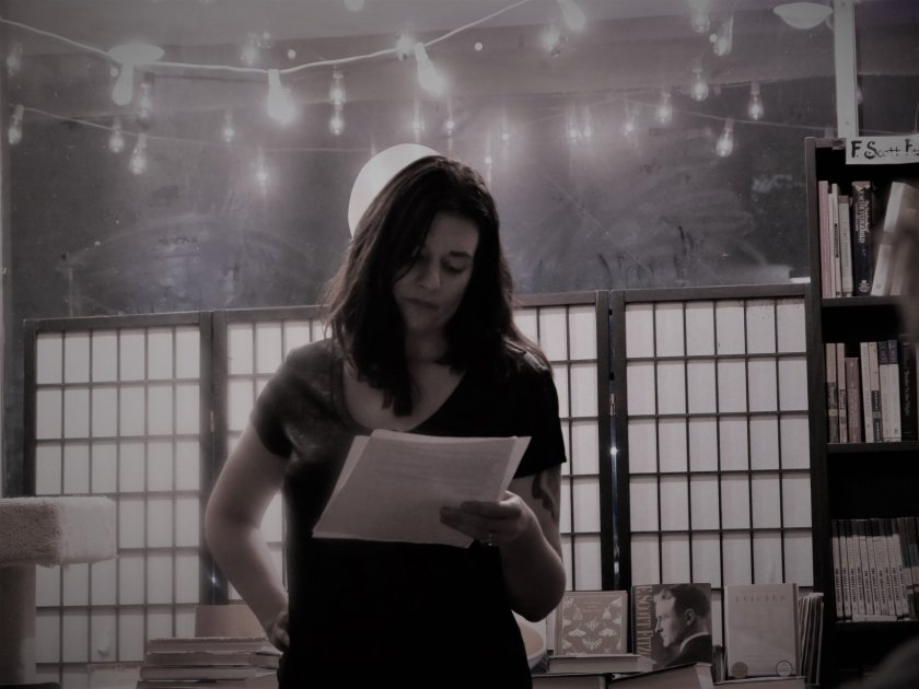 Black and white photo of a dark-haired woman reading poems from a piece of paper.